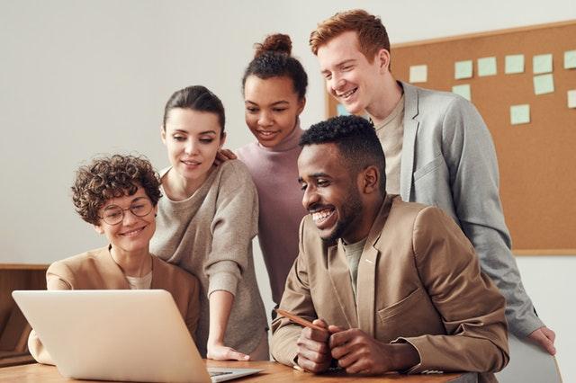 mladší lidé stojí u notebooku